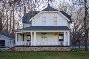 Large white farmhouse with wraparound front porch